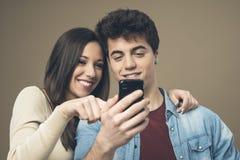 Pares jovenes alegres con el teléfono móvil Foto de archivo