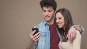 Pares jovenes alegres con el teléfono móvil Foto de archivo libre de regalías