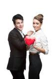 Pares jovenes alegres del asunto que llevan a cabo el corazón rojo Foto de archivo libre de regalías