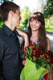 Pares jovenes alegres del retrato con un ramo de rosas rojas Foto de archivo libre de regalías
