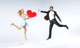 Pares jovenes alegres durante tarjetas del día de San Valentín Fotos de archivo