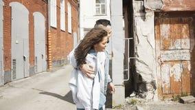 Pares jovenes alegres que caminan en la calle urbana almacen de video