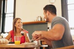 Pares jovenes alegres que desayunan junto Fotografía de archivo libre de regalías