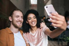 Pares jovenes alegres que hacen las fotos en cámara frontal del teléfono móvil en restaurante Señora afroamericana agradable que  imagenes de archivo