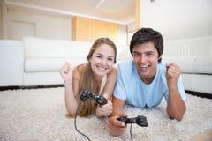 Pares jovenes alegres que juegan a los videojuegos Imágenes de archivo libres de regalías