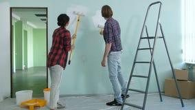 Pares jovenes alegres que pintan interiores de la nueva casa almacen de video