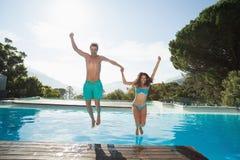 Pares jovenes alegres que saltan en piscina Fotografía de archivo