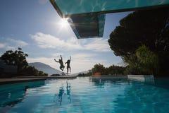 Pares jovenes alegres que saltan en piscina Imagen de archivo libre de regalías