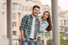 Pares jovenes alegres que se colocan en la calle de la ciudad Fotografía de archivo
