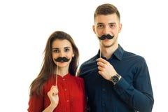 Pares jovenes alegres que se divierten con un bigote de papel Fotografía de archivo libre de regalías