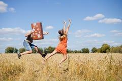 Pares jovenes alegres que se divierten en campo de trigo Hombre emocionado y mujer que corren con la maleta de cuero retra en el  Imágenes de archivo libres de regalías