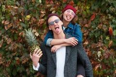 Pares jovenes alegres que se divierten y que ríen junto al aire libre Foto de archivo