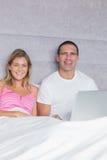 Pares jovenes alegres usando su ordenador portátil junto en cama Foto de archivo libre de regalías