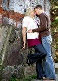 Pares jovenes alrededor a besarse Imagen de archivo libre de regalías