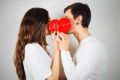 Pares jovenes alrededor a besarse detrás de una caja de regalo en forma de corazón foto de archivo