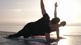 Pares jovenes apuestos, aptos que practican una cierta yoga en frente el mar y que hacen un tablón lateral junto Pares cauc?sicos almacen de video