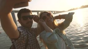 Pares jovenes armoniosos que toman selfies en la playa contra el sol brillante almacen de metraje de vídeo