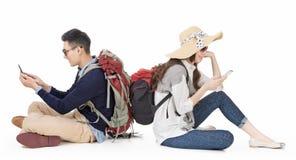 Pares jovenes asiáticos que viajan y que usan el teléfono móvil Fotos de archivo libres de regalías