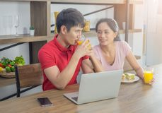 Pares jovenes asiáticos, sentándose en la mesa de comedor feliz, zumo de naranja de consumición sonriente imagenes de archivo