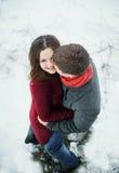 Pares jovenes atractivos en amor en el parque nevoso Fotos de archivo libres de regalías