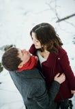 Pares jovenes atractivos en amor en el parque nevoso Imágenes de archivo libres de regalías