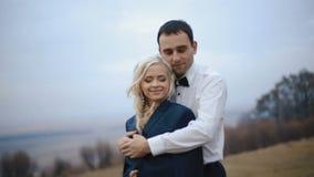 Pares jovenes atractivos en el amor que abraza suavemente en el día frío del otoño El amor se calienta almacen de video