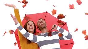 Pares jovenes atractivos en la ropa caliente que sostiene el paraguas y las hojas metrajes