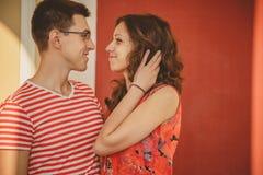 Pares jovenes atractivos Hombre y mujer que sonríen y que miran uno a La muchacha en vestido rojo en el ` s del hombre arma Pares Fotos de archivo libres de regalías