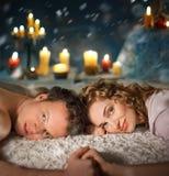 Pares jovenes atractivos puestos en cama. Velas. Foto de archivo libre de regalías