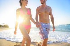 Pares jovenes atractivos que caminan en la playa tropical Foto de archivo libre de regalías
