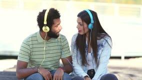 Pares jovenes atractivos que escuchan la música con los auriculares almacen de metraje de vídeo