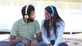 Pares jovenes atractivos que escuchan la música con los auriculares almacen de video