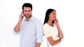 Pares jovenes atractivos que hablan en los teléfonos metrajes