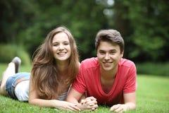 Pares jovenes atractivos que mienten en la hierba Imagenes de archivo