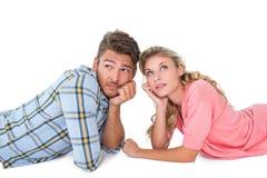 Pares jovenes atractivos que mienten y que piensan Fotografía de archivo libre de regalías