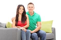 Pares jovenes atractivos que presentan en un sofá Imagen de archivo