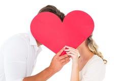 Pares jovenes atractivos que se besan detrás de corazón grande Fotos de archivo libres de regalías