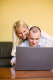 Pares jovenes atractivos que se divierten con la computadora portátil. Foto de archivo