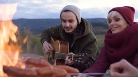 Pares jovenes atractivos que se sientan cerca del fuego y que juegan en la guitarra en los fondos de la montaña almacen de video