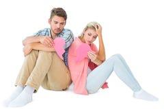Pares jovenes atractivos que se sientan llevando a cabo dos mitades del corazón quebrado Imagen de archivo libre de regalías