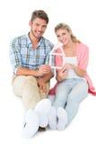 Pares jovenes atractivos que se sientan llevando a cabo un esquema de la casa Fotos de archivo libres de regalías