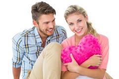 Pares jovenes atractivos que se sientan sosteniendo el amortiguador del corazón Foto de archivo libre de regalías