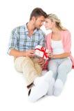 Pares jovenes atractivos que se sientan sosteniendo un regalo Fotos de archivo libres de regalías