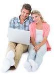 Pares jovenes atractivos que se sientan usando el ordenador portátil Imagen de archivo