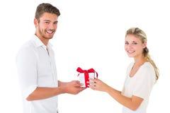 Pares jovenes atractivos que sostienen un regalo Imágenes de archivo libres de regalías