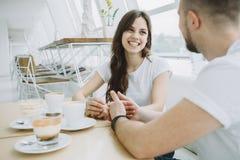 Pares jovenes atractivos una fecha en un café imagenes de archivo