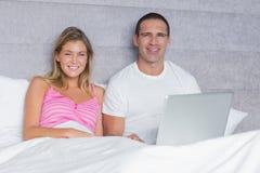 Pares jovenes atractivos usando su ordenador portátil junto en cama Imagen de archivo