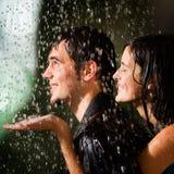 Pares jovenes bajo una lluvia Fotos de archivo