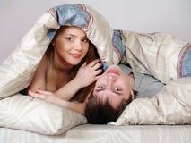 Pares jovenes bajo una manta en una cama Fotos de archivo libres de regalías