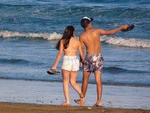 Pares jovenes, barefeet, mirando el mar foto de archivo libre de regalías